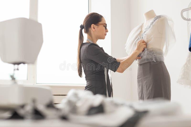 裁缝、裁缝、时尚和陈列室概念-女性在时装模特的时尚编辑测量的材料侧视图  图库摄影