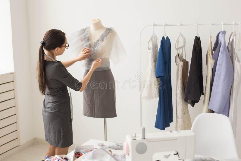 裁缝、裁缝、时尚和陈列室概念-有天才的女性裁缝画象与纺织品一起使用为 免版税库存图片