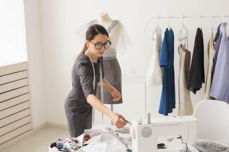 裁缝、裁缝、时尚和陈列室概念-有天才的女性裁缝画象与纺织品一起使用为 免版税库存照片