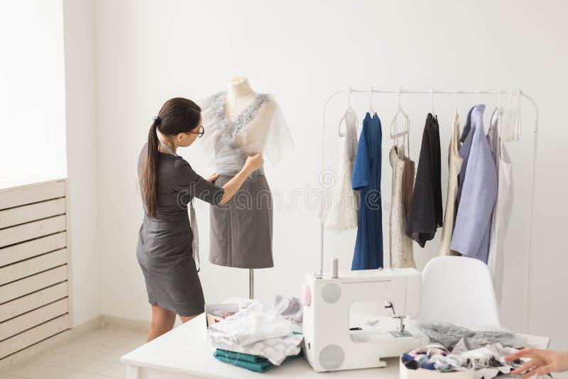 裁缝、裁缝、时尚和陈列室概念-有天才的女性裁缝画象与纺织品一起使用为 库存图片