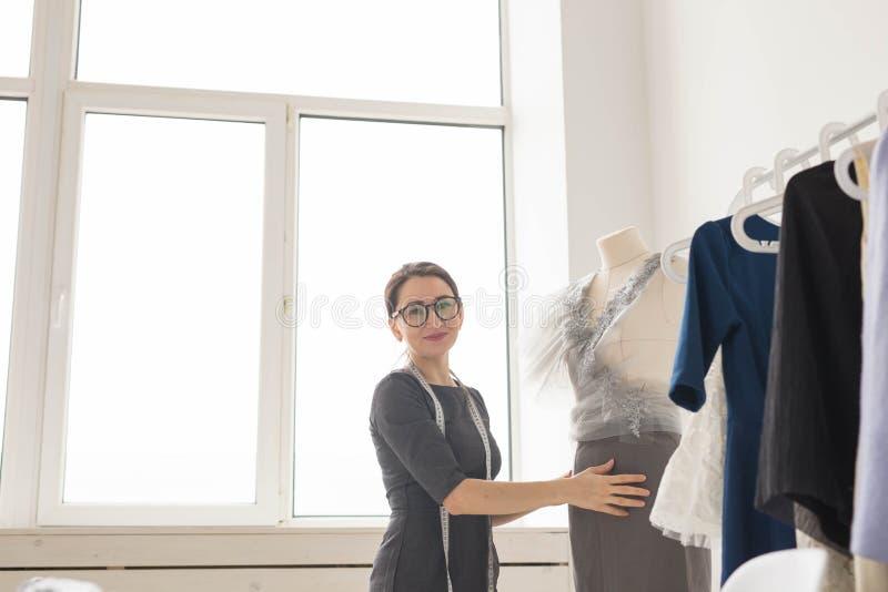 裁缝、裁缝、时尚和陈列室概念-有天才的女性裁缝画象与纺织品一起使用为 库存照片