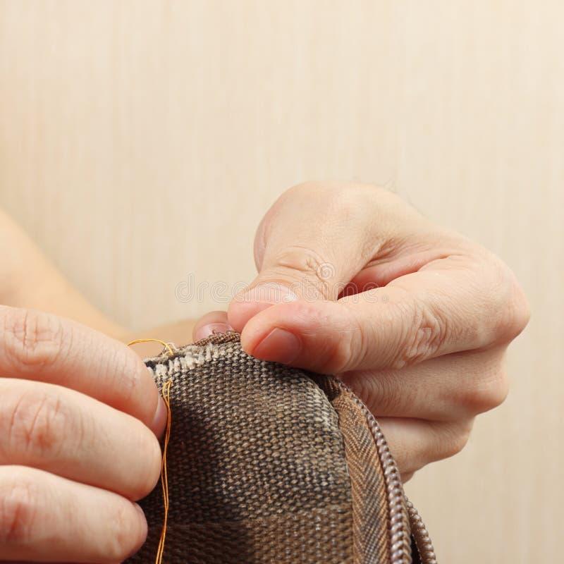 裁缝修理耐久的布料袋子的手与针关闭的 免版税库存图片