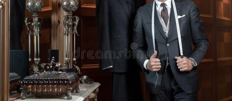 裁缝递昂贵的剪裁的各自的衣服 免版税库存图片