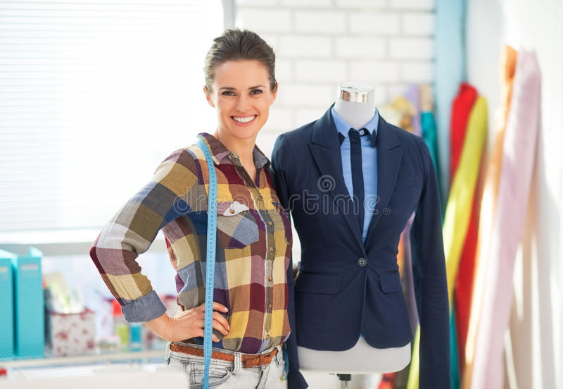 裁缝画象在时装模特附近的在衣服 免版税库存照片