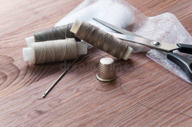 裁缝` s书桌 老缝合的木鼓或丝球在一个老木工作台有剪刀的 免版税库存照片