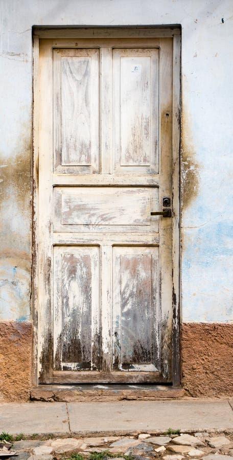 裂化的白色绘了在蓝色被弄脏的墙壁上的门 免版税库存照片