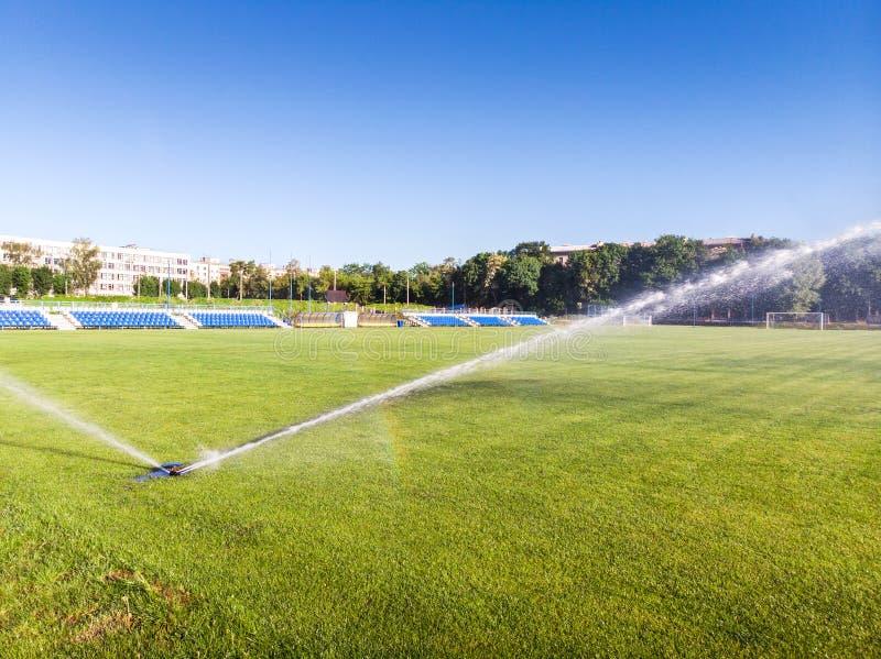装喷水器浇灌对草地在橄榄球场内 免版税图库摄影