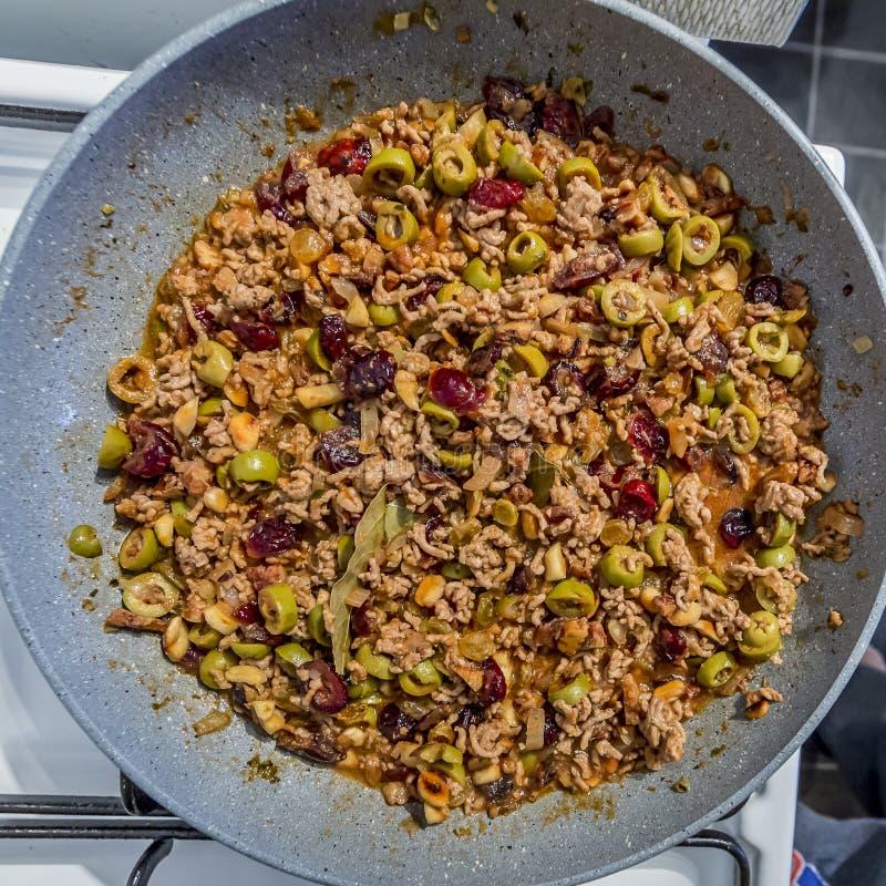 装填的图象用绞肉、橄榄、葡萄干、蔓越桔、核桃、杏仁、在平底锅的月桂叶和香料 库存图片