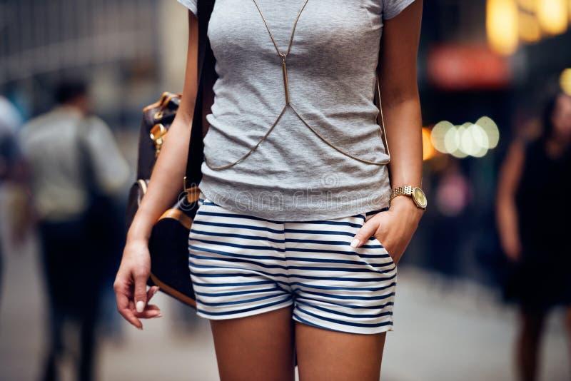 装备细节时尚典雅时髦妇女摆在 有短的镶边蓝色和白色短裤的,灰色t-shir女性夏天成套装备 库存照片