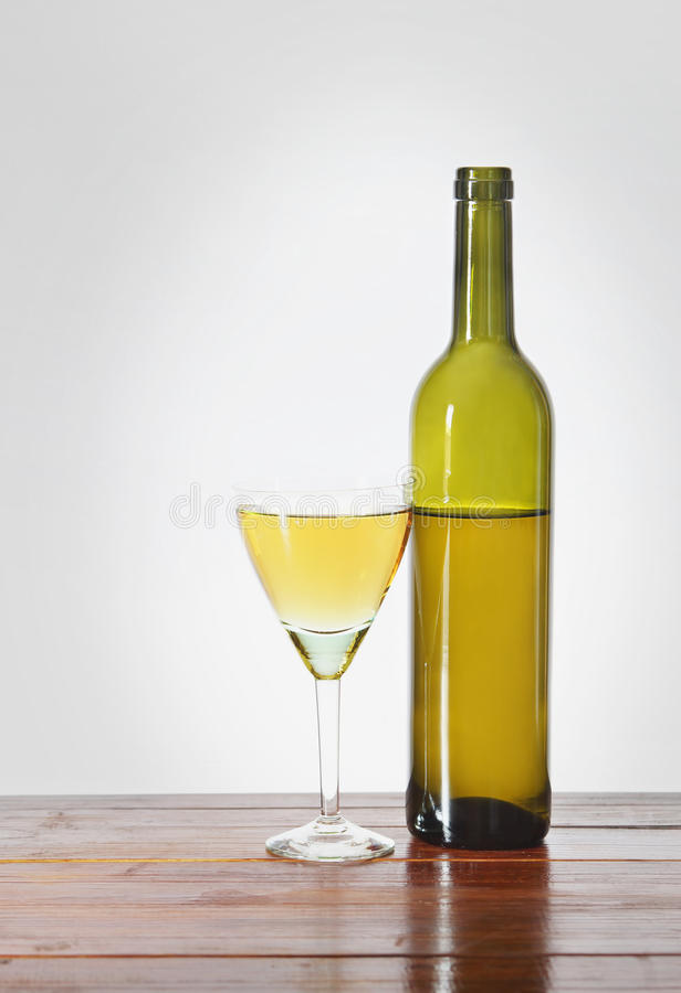 装瓶和一杯在木桌上的酒 图库摄影