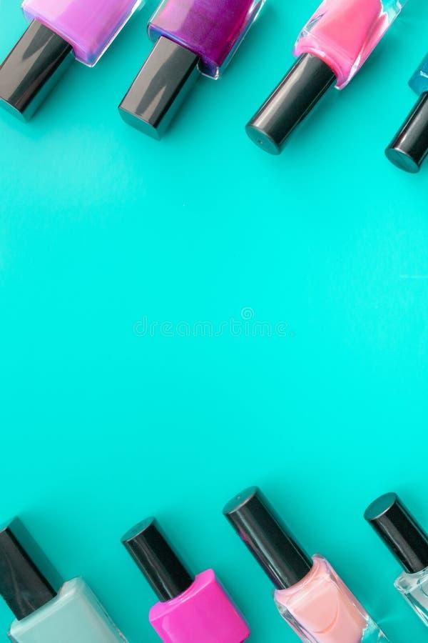 装瓶指甲油 一个小组在绿色背景的明亮的指甲油 空的空间在中部 库存图片