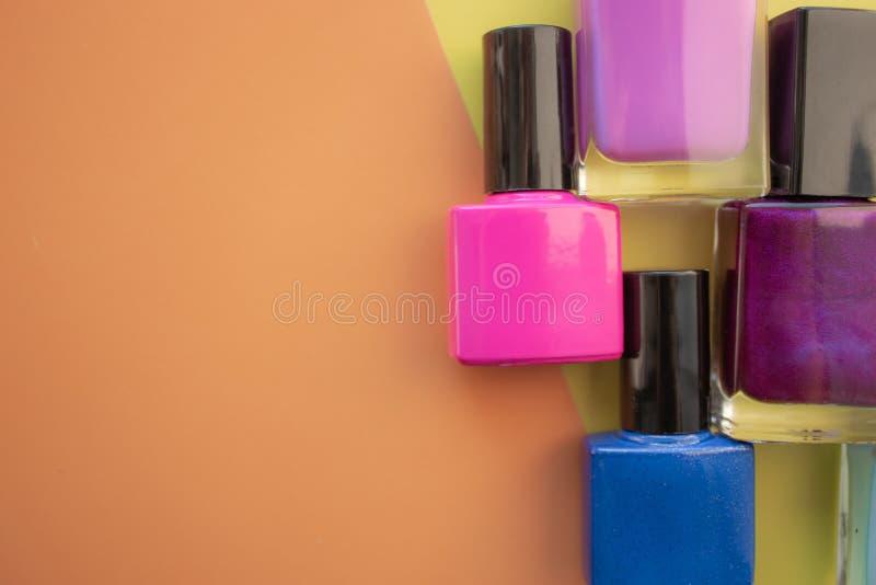 装瓶指甲油 一个小组在色的,黄色背景的明亮的指甲油 在左边的空的空间 库存图片