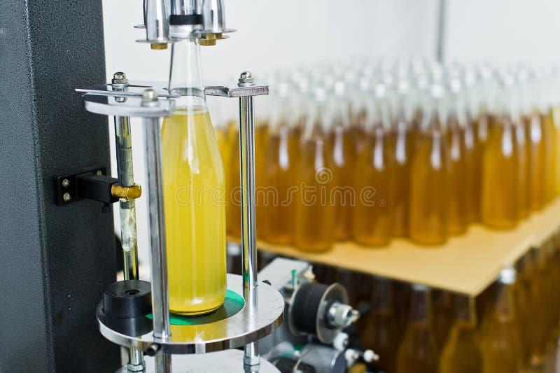 装瓶的工厂-处理和装瓶的啤酒的啤酒瓶线到瓶里 免版税库存图片