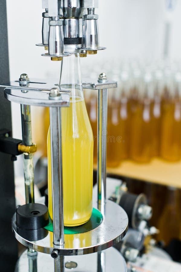装瓶的工厂-处理和装瓶的啤酒的啤酒瓶线到瓶里 免版税图库摄影