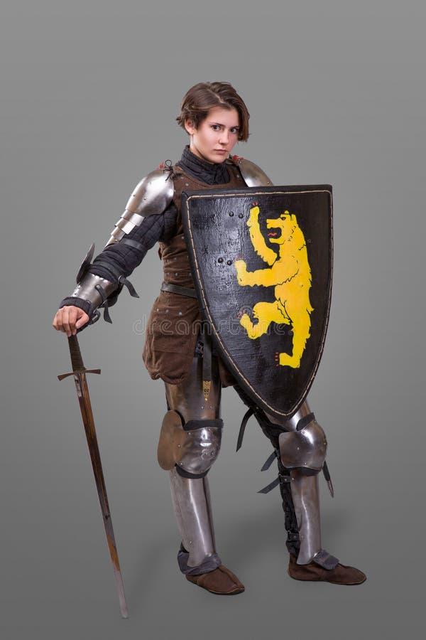 装甲的女孩有在灰色背景的剑骑士wuth盾的 图库摄影