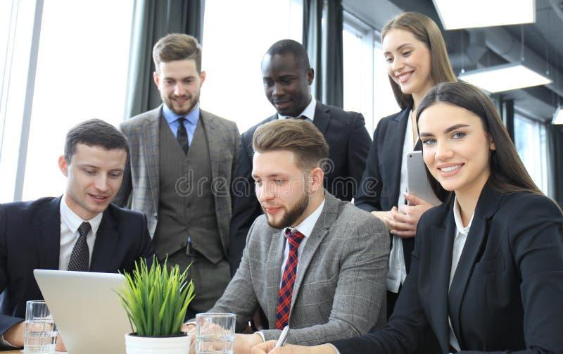 装箱的 小组一起看膝上型计算机的商人 看照相机的一个女商人 库存照片