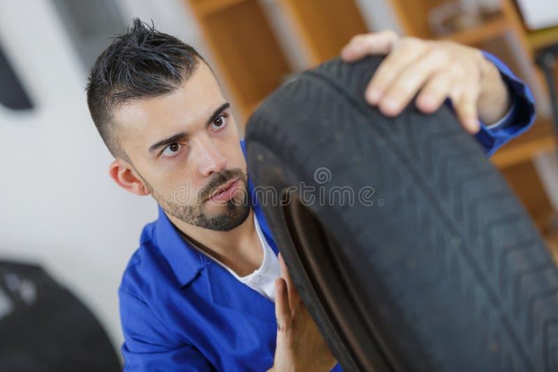 装胎检查在车胎的技工踩深度 库存图片