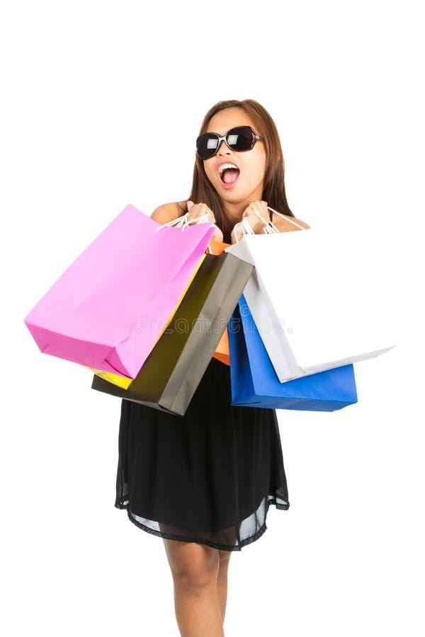 装腔作势地说在照相机v的亚洲女性顾客袋子 免版税库存图片
