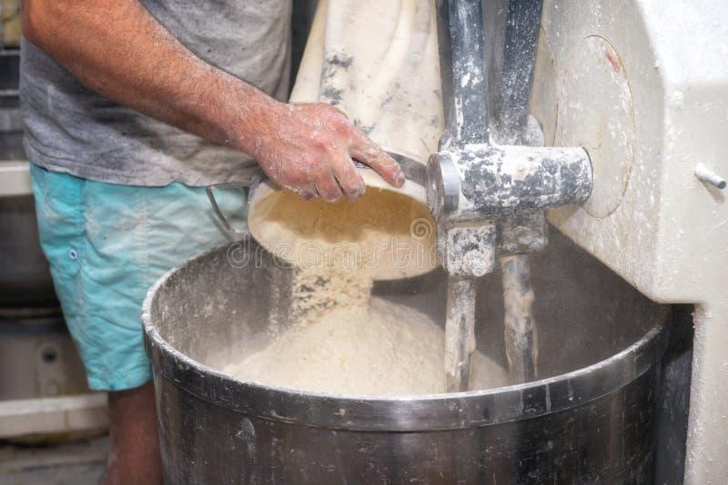 装货面粉到一台工业面包店揉面机里 免版税库存图片
