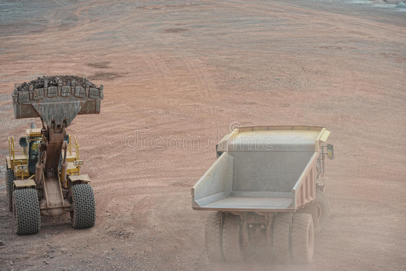 装载倾销者卡车的挖掘机用石头 免版税图库摄影