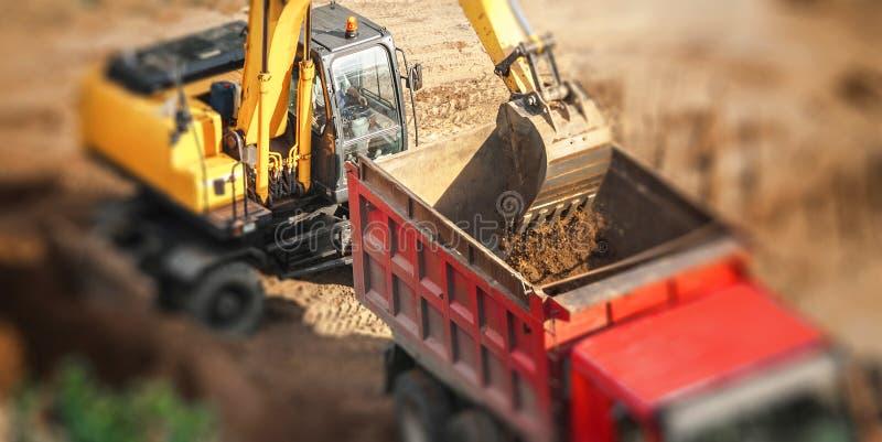装载倾销者卡车的挖掘机 免版税图库摄影