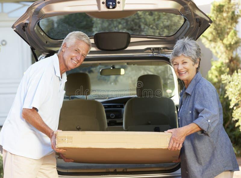 装载大包裹的资深夫妇入汽车后面  免版税库存图片