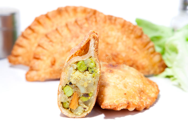 装载用煮沸的豌豆的酥脆菜Samosa 库存图片