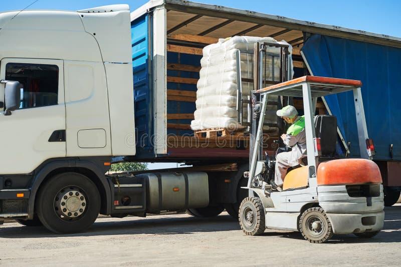 装载的工作 有装载和卡车卡车的铲车 免版税图库摄影