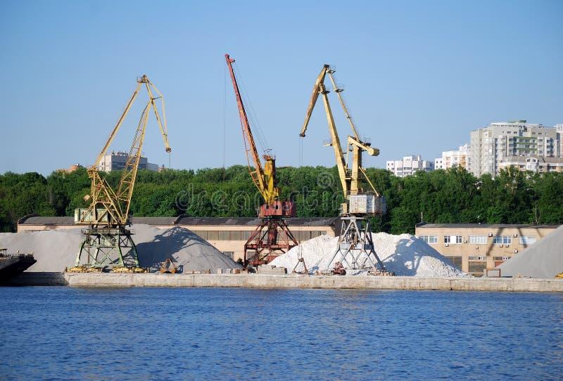 装载的驳船立场的工业起重机在巨大的堆背景沙子和石渣在希姆基水库的银行 免版税库存图片