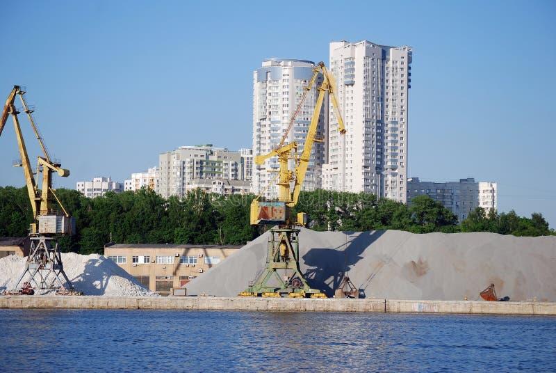 装载的驳船立场的工业起重机在巨大的堆背景沙子和石渣在希姆基水库的银行 免版税库存照片