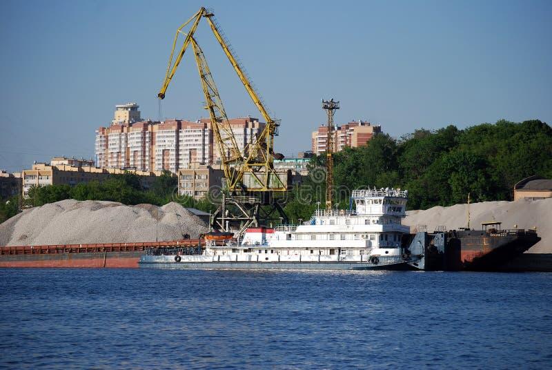 装载的驳船立场的工业起重机在巨大的堆背景沙子和石渣在希姆基水库的银行 库存图片
