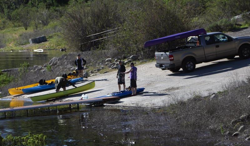 装载皮船的两个人入Cachuma湖,圣巴巴拉县 免版税库存图片