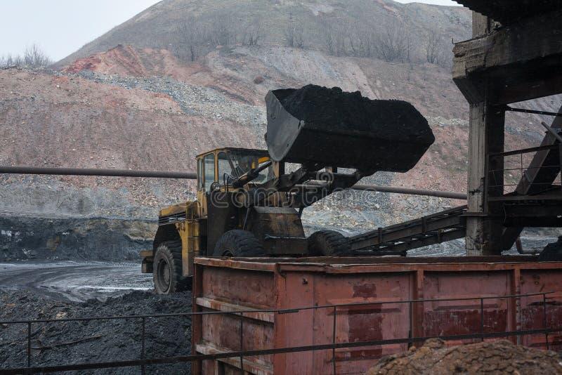 装载者装载煤炭入有轨机动车 免版税库存照片