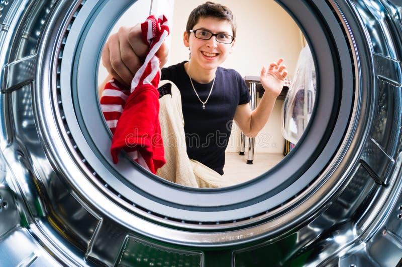 装载衣裳的滑稽的人对洗衣机 免版税图库摄影