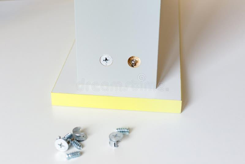 装配厨房箱子的过程 箱子的门面的连接与墙壁 一把锁已经是站立, 免版税库存照片