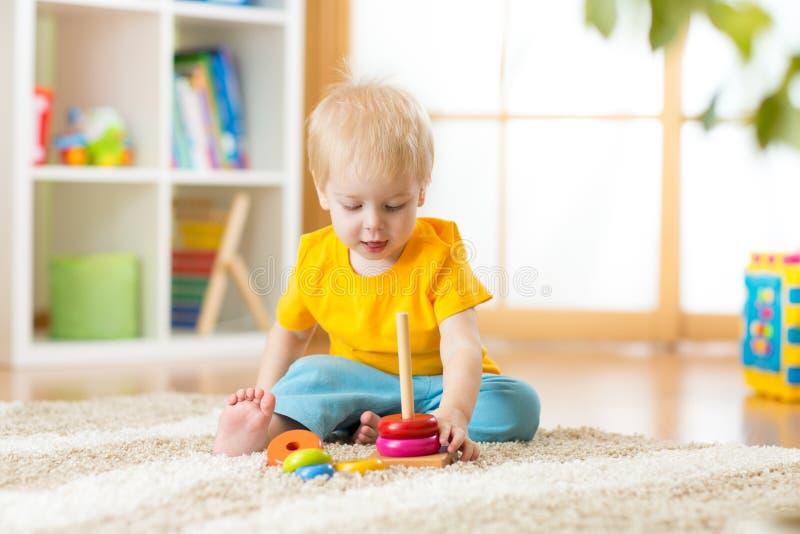 装配在地板上的逗人喜爱的儿童小孩男孩画象五颜六色的金字塔玩具在客厅 库存照片