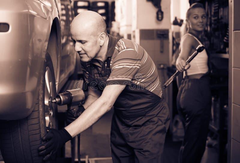 装配新的轮胎的成人人技术员对汽车 免版税库存图片