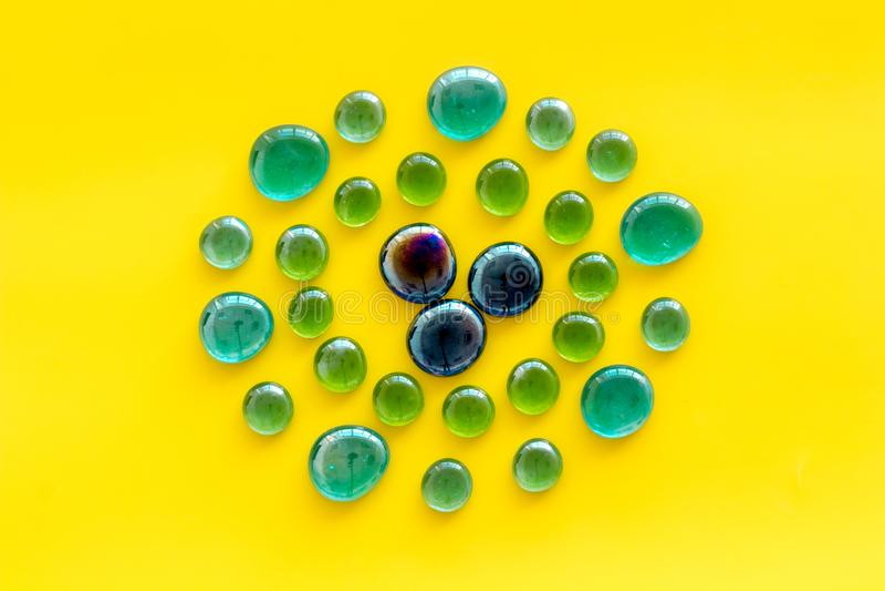 装饰、创造性和工艺的发光的玻璃石头在黄色背景顶视图 免版税库存图片