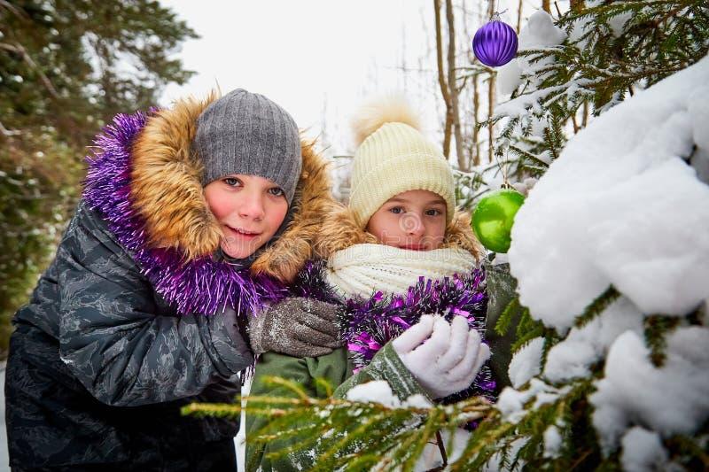 装饰一棵圣诞树的孩子在雪森林里在一个冬日 少年获得休息和乐趣在室外的周末 库存照片