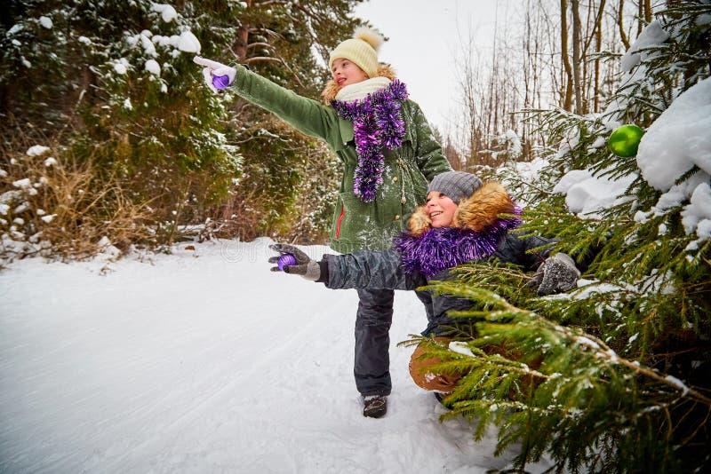 装饰一棵圣诞树的孩子在雪森林里在一个冬日 少年获得休息和乐趣在室外的周末 库存图片