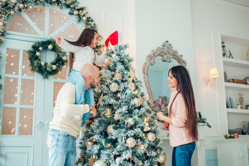 装饰与boubles的愉快的家庭一棵圣诞树在客厅 免版税库存照片