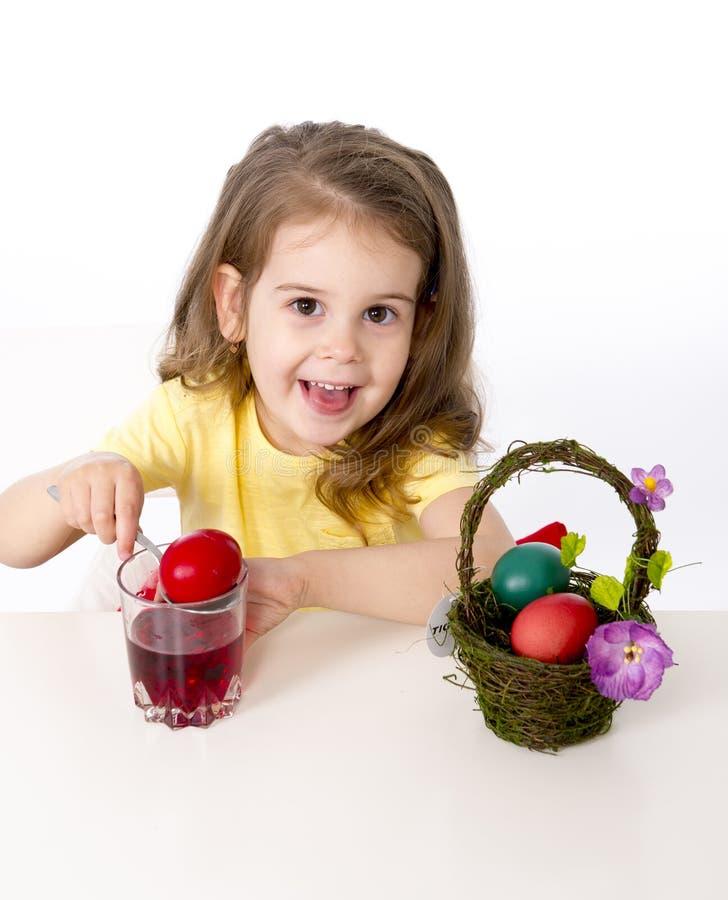 装饰传统复活节彩蛋的小女孩 免版税库存照片
