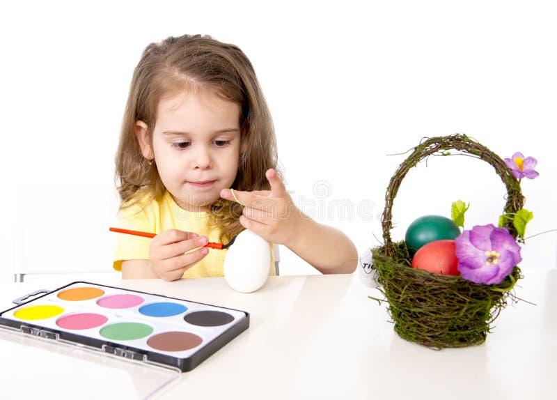 装饰传统复活节彩蛋的小女孩 免版税库存图片