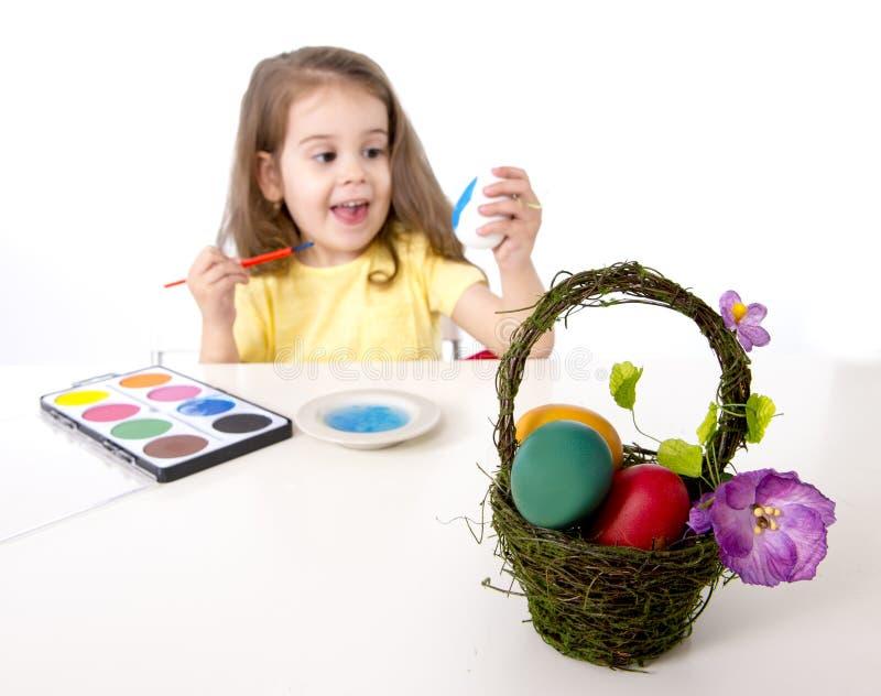 装饰传统复活节彩蛋的小女孩 免版税图库摄影
