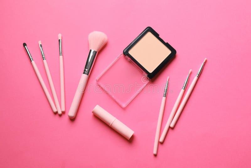 装饰化妆用品和刷子申请的构成在颜色背景,顶视图 库存图片