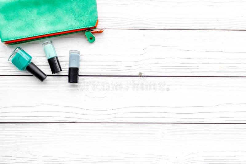 装饰化妆用品设置与秀丽袋子,并且在白色书桌背景顶视图拷贝空间指甲油 库存照片