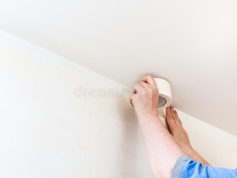 装饰员在墙壁上的固定磁带在绘前 库存照片