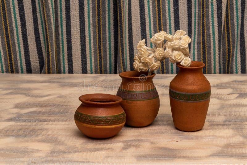 装饰品和小花的黏土水罐 图库摄影