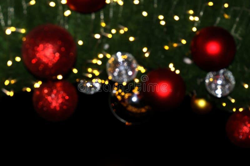 装饰圣诞快乐和新年好被弄脏的背景红色球吊Bokeh光  免版税图库摄影