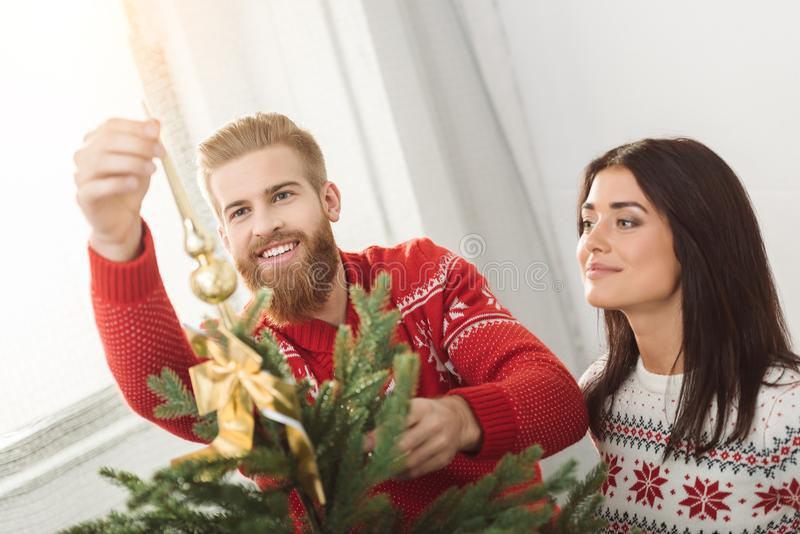 装饰圣诞树的夫妇 免版税库存照片